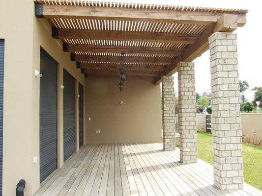 פרגולות מקורות עץ גושני בגוון מיושן עם במבוק מושחל להצללה, חיבור לקיר פרזולי ברזל